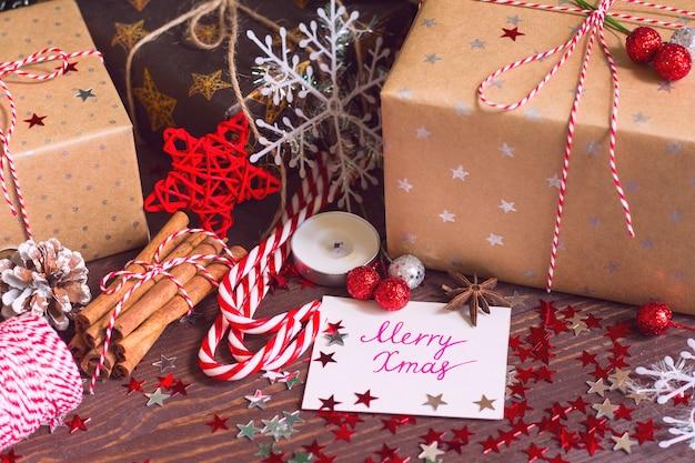 Bożenarodzeniowy wakacyjny prezenta pudełko z pocztówką wesoło xmas na dekorującym świątecznym stole
