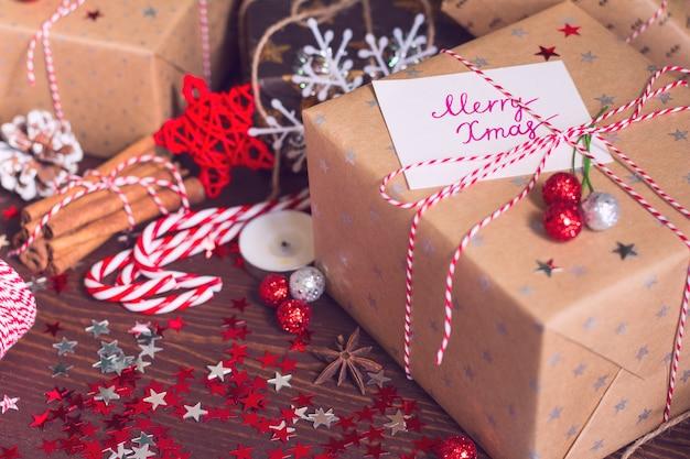Bożenarodzeniowy wakacyjny prezenta pudełko z pocztówkową wesoło xmas na dekorującym świątecznym stole z sosnowymi rożkami cynamonowymi