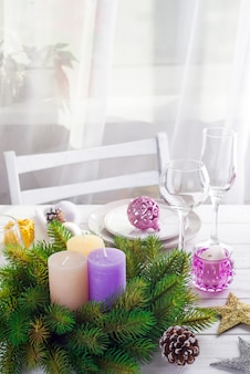 Bożenarodzeniowy wianek z kolorowymi dużymi świeczkami na stole z bożenarodzeniowym stołowym położeniem