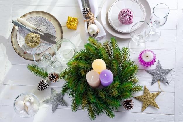 Bożenarodzeniowy wianek z kolorowymi dużymi świeczkami na stole