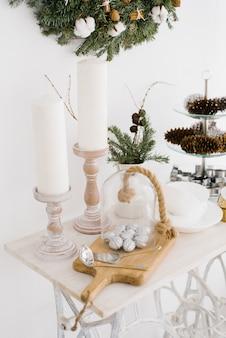 Bożenarodzeniowy wystrój na białym stole. świece, srebrne orzechy włoskie na desce do krojenia