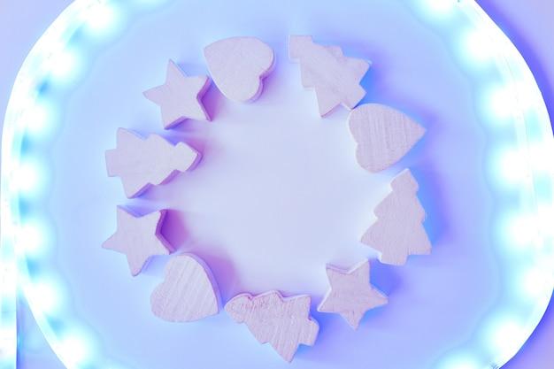Bożonarodzeniowa rama z drewnianymi gwiazdami i drzewami, serca z światłami na bielu