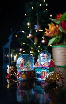Bożonarodzeniowa scena z drzewem, światłami i śnieżną kulą ziemską. selektywna ostrość