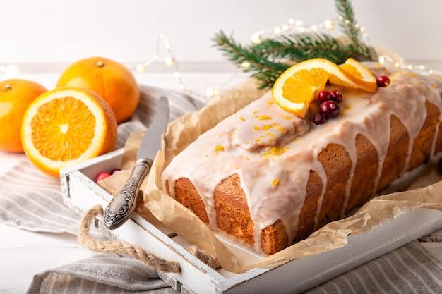 Bożonarodzeniowe ciasto pomarańczowe z żurawiną i lukrem cukrowym na rustykalnym drewnianym tle