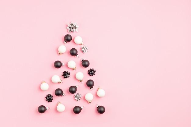 Bożonarodzeniowe ornamony ułożone w kształcie choinki na różowej powierzchni