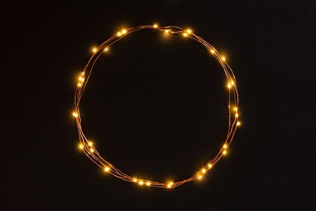 Bożonarodzeniowe światła girlandy granica na czarnym tle.