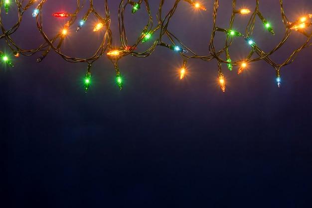 Bożonarodzeniowe światła na błękitnym tle z copyspace
