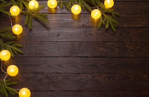 Bożonarodzeniowe światła z jedlinowymi branchs na ciemnym drewnie