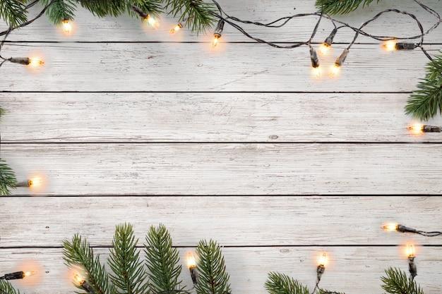 Bożonarodzeniowe światła żarówka i sosna opuszczają dekorację na białej drewnianej desce, ramy granicy projekt. wesołych świąt bożego narodzenia i nowego roku wakacje tło. widok z góry.