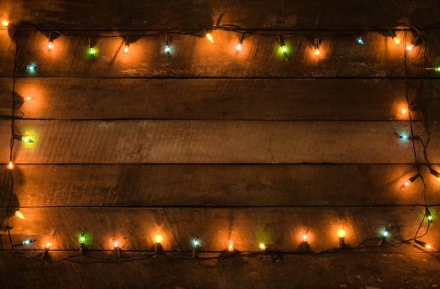 Bożonarodzeniowe światła żarówki dekoracja na starej drewnianej desce, ramy granicy projekt. wesołych świąt bożego narodzenia i nowego roku wakacje tło. odcień rocznika.