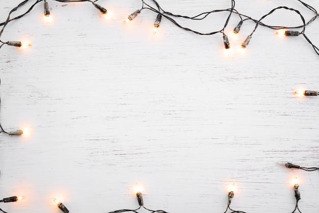 Bożonarodzeniowe światła żarówki ramy dekoracja na białym drewnie. wesołych świąt bożego narodzenia i nowego roku wakacje tło. widok z góry
