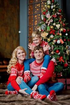 Bożonarodzeniowy portret rodzinny w czerwonych tradycyjnych swetrach w domowym salonie, rodzicach i dziecku z pudełkiem.