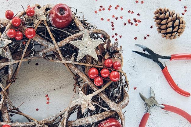 Bożonarodzeniowy wieniec wykonany z gałęzi ozdobionych złotymi drewnianymi gwiazdkami i czerwonymi jagodowymi bąbelkami. kreatywne hobby rzemieślnicze. wykonywanie ręcznie robionych ozdób choinkowych. klasa widoku z góry z metalowymi szczypcami, szczypcami