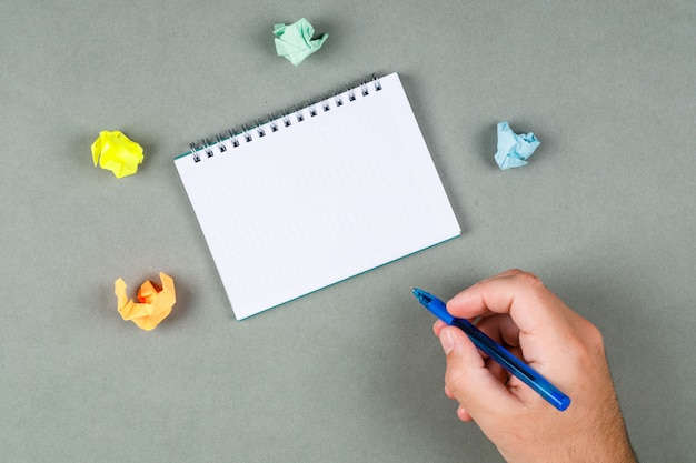Brać notatki pojęcie z notatnikiem, poszarpane notatki na szarego tła odgórnym widoku. dłoń trzymająca długopis. miejsce na tekst. obraz poziomy