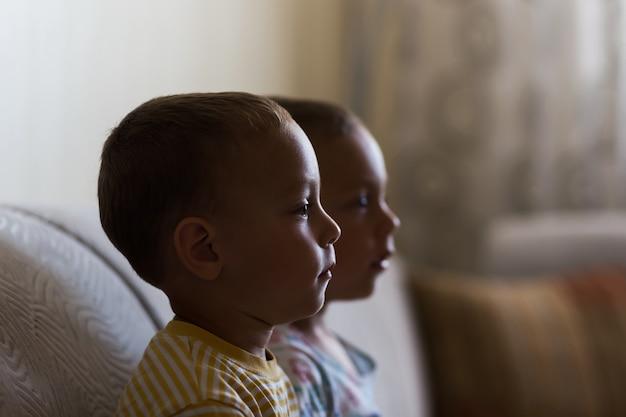 Bracia bliźniacy siedzi na kanapie
