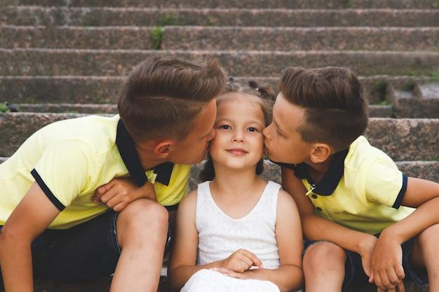 Bracia całują siostrę w policzek