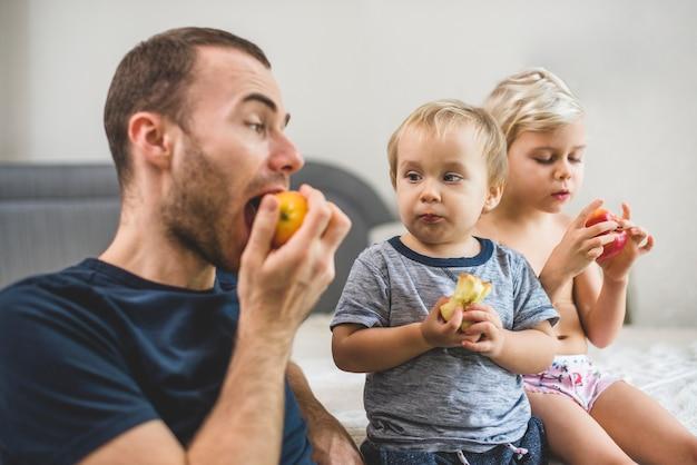 Bracia jedząc jabłko