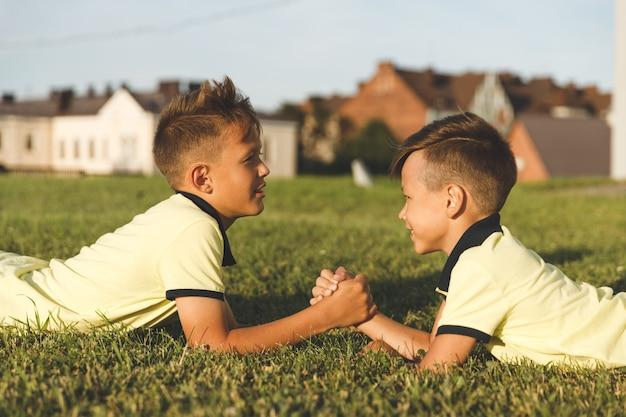 Bracia leżący na trawie uprawiają siłowanie na rękę.