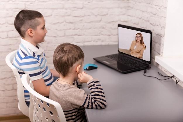Bracia patrzą na laptopa podczas nauki w pokoju dziecięcym.