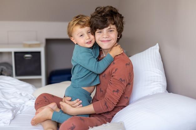 Bracia siedzą rano w łóżku po przebudzeniu i przytulaniu. czuły starszy brat. szczęśliwa rodzina.