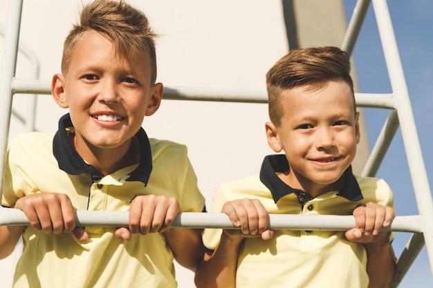 Bracia z fryzurami siedzą na balkonie. światło słoneczne