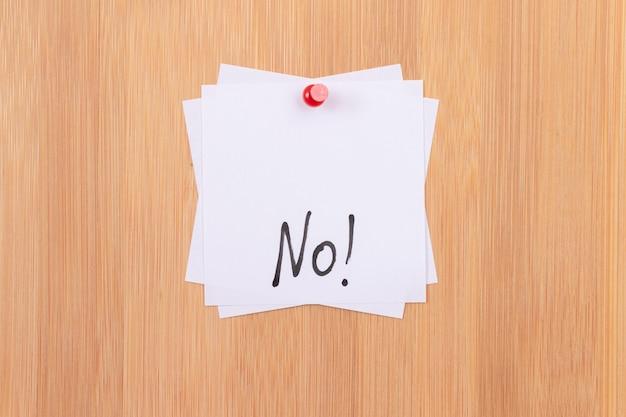 Brak białych karteczek z napisem bez przypięcia do drewnianej tablicy dyskusyjnej
