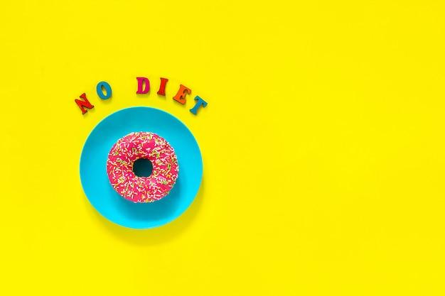 Brak diety i różowy pączek na niebieskim talerzu na żółtym