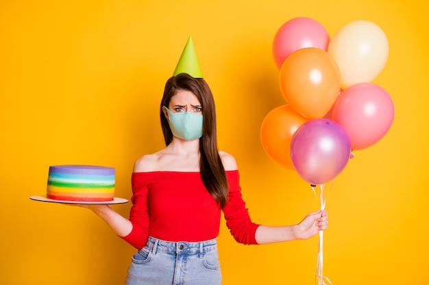 Brak gościnnej imprezy rocznicowej. zdenerwowana dziewczyna w masce medycznej świętować urodziny trzymać balony ciasto sfrustrowany nosić czerwony dorywczo top denim dżinsy stożek na białym tle nad jasnym połyskiem kolor tła