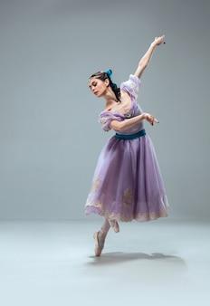 Brak grawitacji. piękna współczesna tancerka balowa na białym tle na szarej ścianie. zmysłowy profesjonalny artysta tańczący walza, tango, slowfox i quickstep. elastyczny i nieważki.
