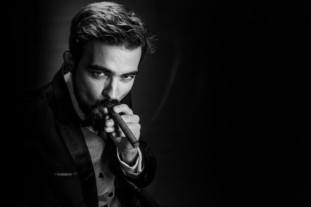 Brak i biały portret brodatego dżentelmena palenia w garniturze