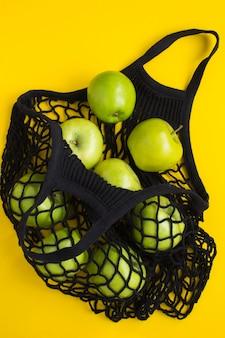 Brak koncepcji plastikowej torby. siateczkowa czarna torba na zakupy z zielonymi jabłkami na żółtej powierzchni