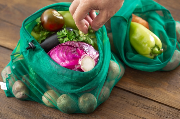 Brak koncepcji plastikowej torby. siatkowe torby spożywcze różne warzywa na drewnianym stole