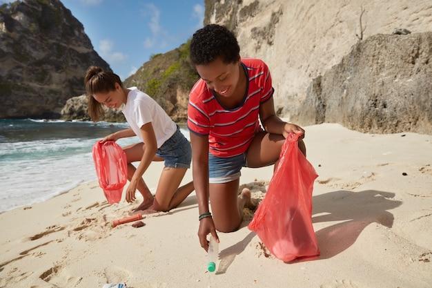 Brak koncepcji plastiku. dwie międzyrasowe młode kobiety zbierają śmieci w workach na śmieci z plaży