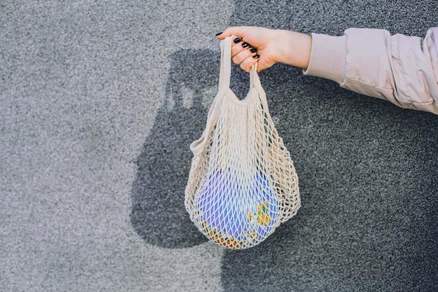Brak koncepcji plastiku. ręce trzymając globus planeta ziemia w torbie netto.