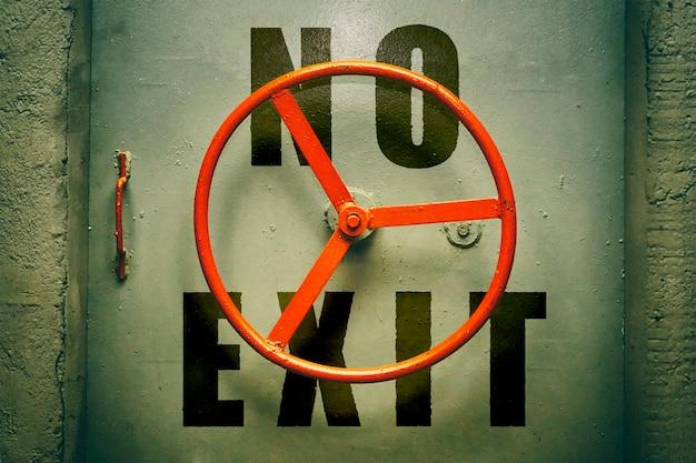 Brak ostrzeżenia o wyjściu na hermetycznych drzwiach bunkra z czerwonym pokrętłem