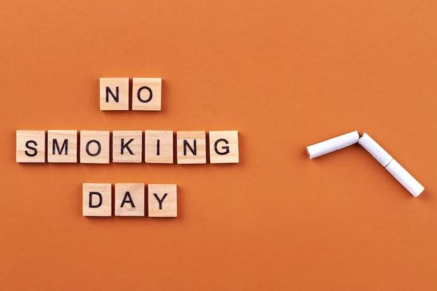 Brak plakatu dnia tytoniu. zepsuty papieros i drewniane klocki z literami na białym tle na pomarańczowym tle.