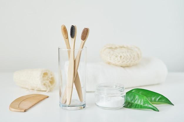 Brak plastikowej koncepcji zero odpadów. ekologiczne drewniane bambusowe szczoteczki do zębów w szklance, ręczniku, proszku do zębów i myjce