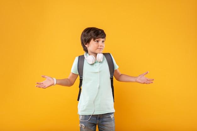 Brak pomysłu. zdumiony ciemnowłosy chłopak w słuchawkach i tornister, myślący