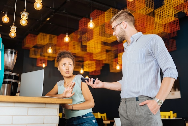 Brak pożądania. ciemnowłosa stylowa kobieta nie ma ochoty rozmawiać przez telefon, siedząc obok swojego szefa