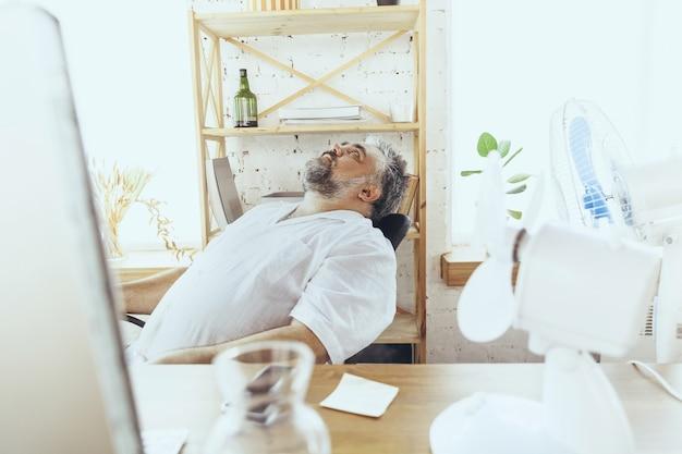 Brak ratowania menedżera biznesmena w biurze z komputerem i wentylatorem chłodzącym uczucie gorąca?