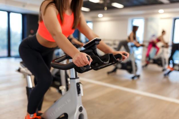 Brak twarzy portret młodej kobiety szczupłej w treningu sportowej na rowerze stacjonarnym w siłowni.