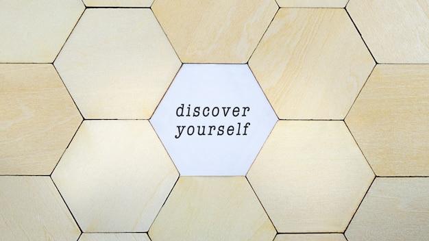 Brakujący drewniany sześciokąt z puzzli, odsłaniający słowo: odkryj siebie na nowo w konceptualnym obrazie rozwoju osobistego i odkrywania siebie