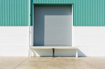 Brama rolowana i rampa rampy dokującej na zewnątrz budynku fabrycznego