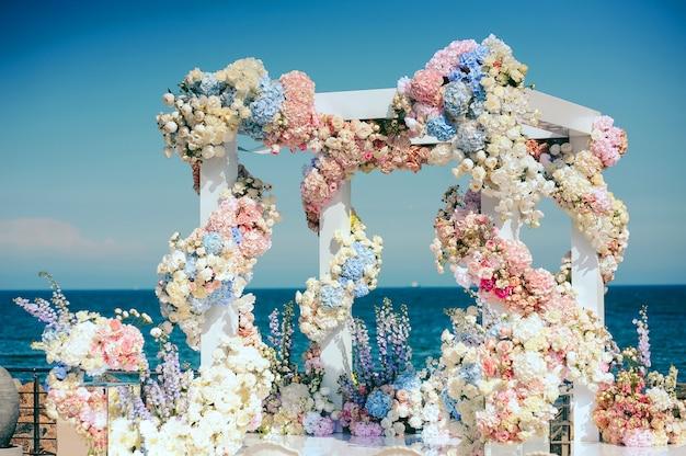 Brama ślubna z dużą ilością różnych kwiatów