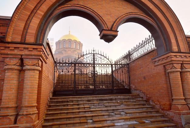 Brama wjazdowa na teren cerkwi, złota kopuła we mgle. rosyjsko-bizantyjski styl architektury. syberia, rosja