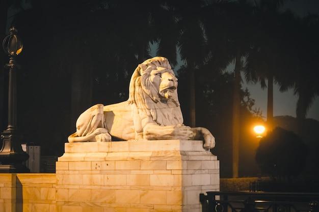 Brama wjazdowa z białymi marmurowymi lwami pomnika architektonicznego victoria memorial i muzeum w kalkucie w indiach. rzeźba białego lwa w nocnym świetle.
