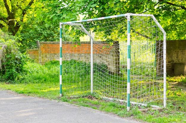 Brama z piłką na boisku do piłki nożnej w parku otoczonym zielenią