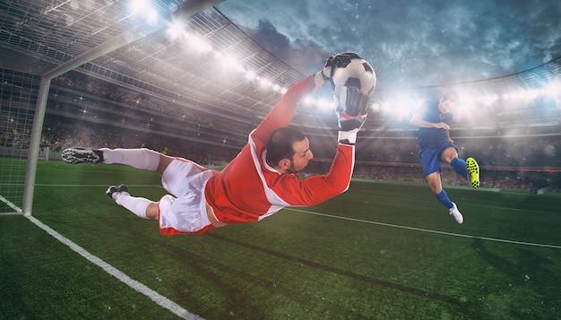 Bramkarz łapie piłkę na stadionie podczas meczu piłki nożnej