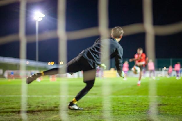 Bramkarz łapie piłkę podczas obrony w bramce podczas meczu piłkarskiego
