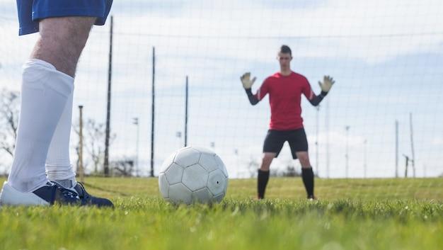 Bramkarz na czerwono czeka na napastnika, aby uderzyć piłkę